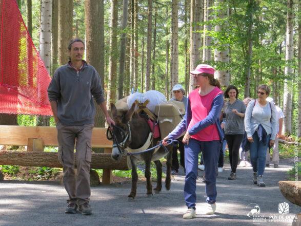 Un groupe de promeneurs en situation de handicap mental (association M'Arche en choeur) suivent un guide et son âne.